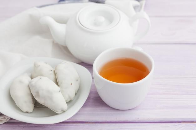 Xícara de chá com biscoitos sobre fundo de madeira lilás