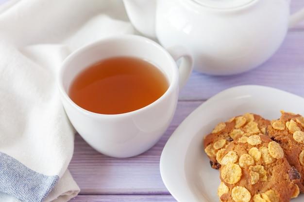 Xícara de chá com biscoitos sobre madeira lilás