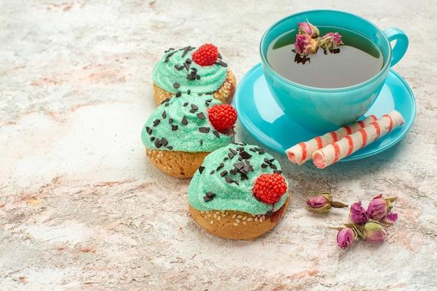 Xícara de chá com bolos cremosos no fundo branco chá sobremesa biscoito torta de vista frontal