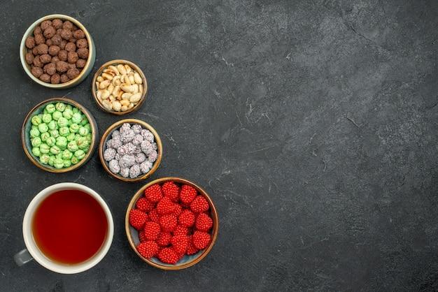 Xícara de chá com bombons de açúcar no espaço cinza com vista superior