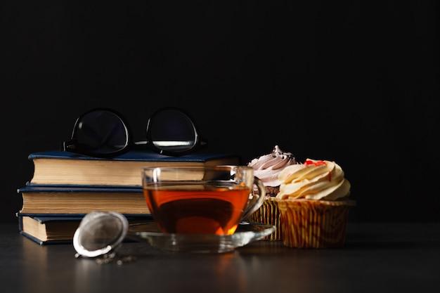 Xícara de chá com botões de rosa secos e livros antigos à noite