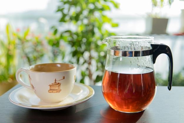 Xícara de chá com bule de chá.