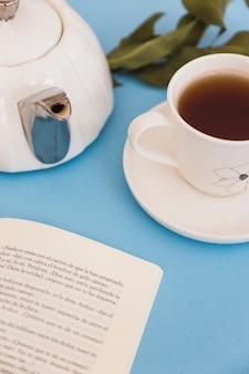 Xícara de chá com bule e livro