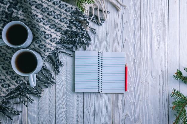 Xícara de chá com cachecol e caderno sobre fundo de natal