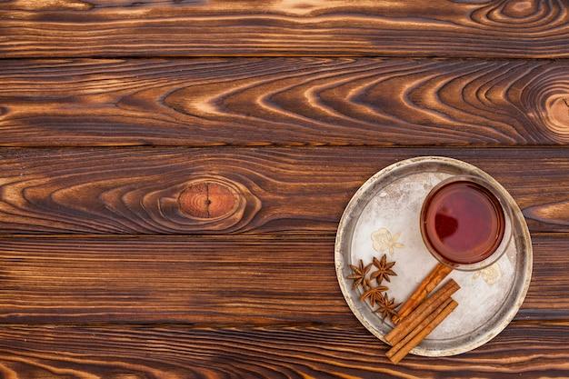 Xícara de chá com canela e anis no prato