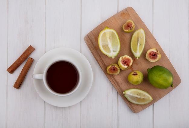 Xícara de chá com canela e figos com fatias de limão em uma tábua de corte no fundo branco, vista de cima