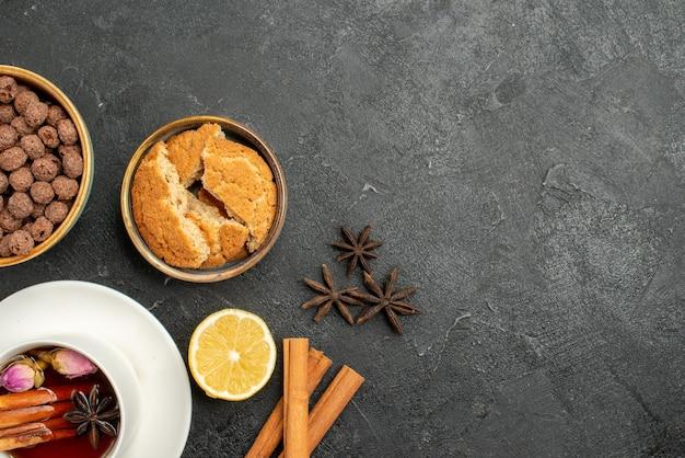 Xícara de chá com canela e flocos na superfície cinza-escuro de chá com canela e doce de cerimônia de bebida de chá