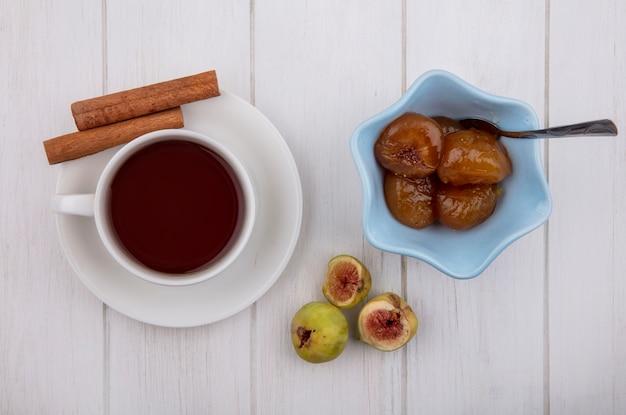 Xícara de chá com canela e geléia de figo em pires com colher de chá no fundo branco.