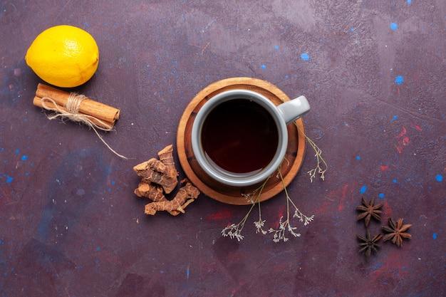 Xícara de chá com canela e limão em fundo escuro foto colorida