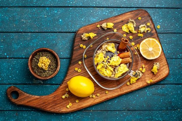 Xícara de chá com canela e limão na mesa azul com vista superior