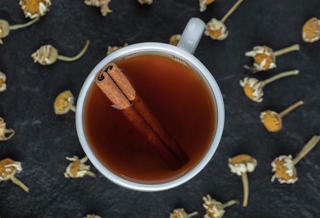 Xícara de chá com canela e pilha de camomilas secas.