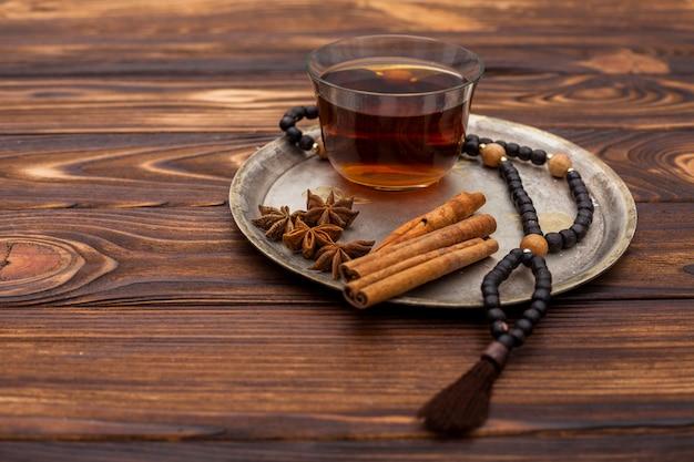 Xícara de chá com canela e rosário na placa