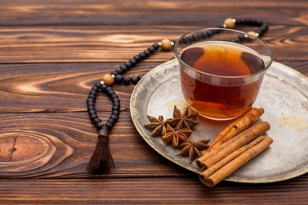 Xícara de chá com canela e rosário
