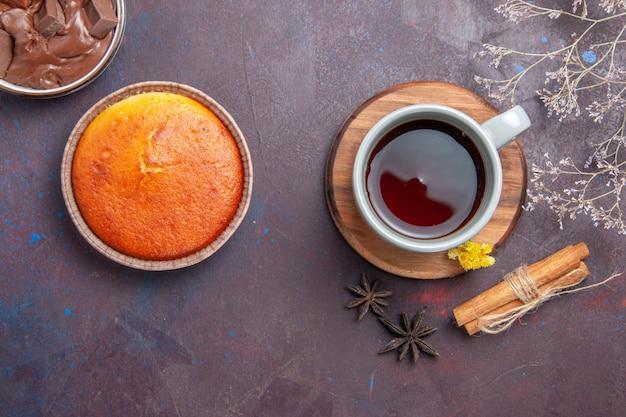 Xícara de chá com canela na mesa escura de frente para beber chá de cor doce