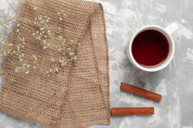 Xícara de chá com canela na superfície branca da vista superior