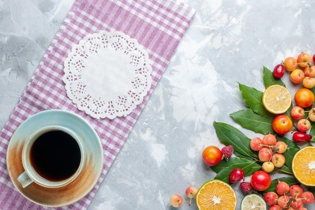 Xícara de chá com cerejas e outras frutas na mesa clara com vista de cima
