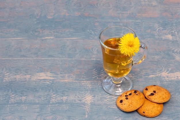 Xícara de chá com chá de ervas e biscoitos de dente de leão e passas amarelos sobre fundo azul de madeira, copie o espaço. chá de ervas saudável nos dias quentes de verão. conceito de comida saudável