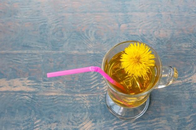 Xícara de chá com chá de ervas e dente de leão amarelo e palha rosa sobre fundo azul de madeira iluminado por raios de sol, copie o espaço. bebida de ervas ecologicamente correta, estilo de vida saudável.