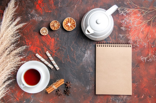 Xícara de chá com chaleira na mesa escura com vista de cima