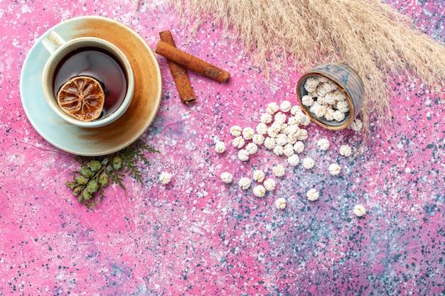 Xícara de chá com confitures doces brancos e canela na vista de cima na superfície rosa claro