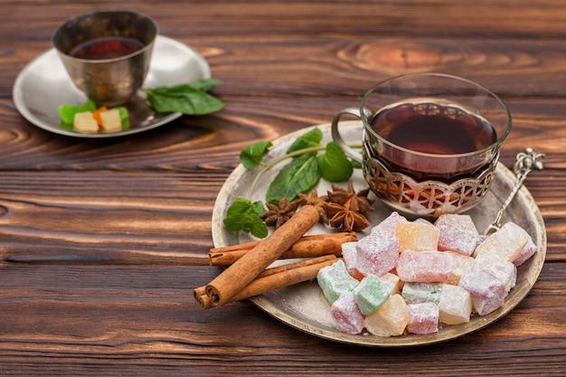 Xícara de chá com delícias turcas na mesa de madeira