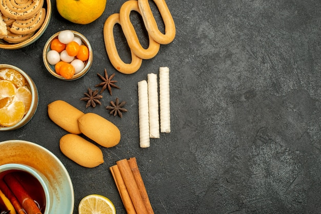 Xícara de chá com doces, biscoitos e frutas na mesa cinza biscoito doce de chá