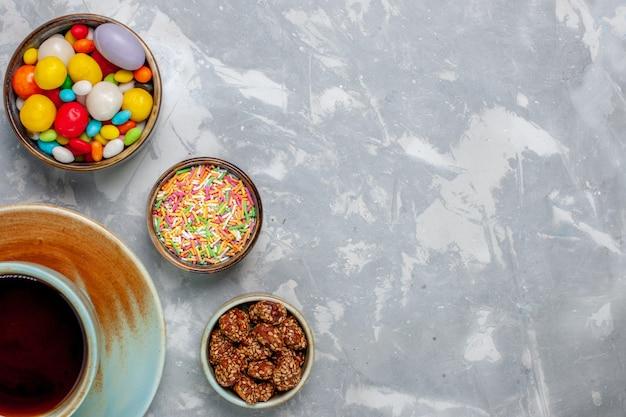 Xícara de chá com doces coloridos em uma mesa branca clara bombom goodie torta de açúcar doce