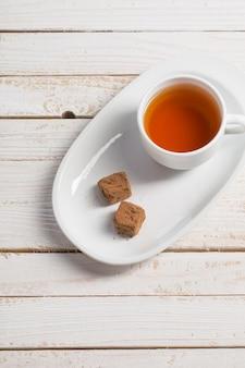 Xícara de chá com doces de chocolate na mesa de madeira