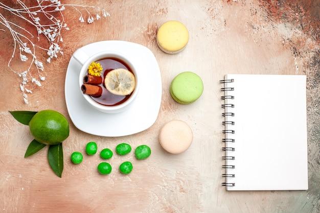 Xícara de chá com doces e macarons na mesa clara de biscoitos de limão e chá com vista de cima