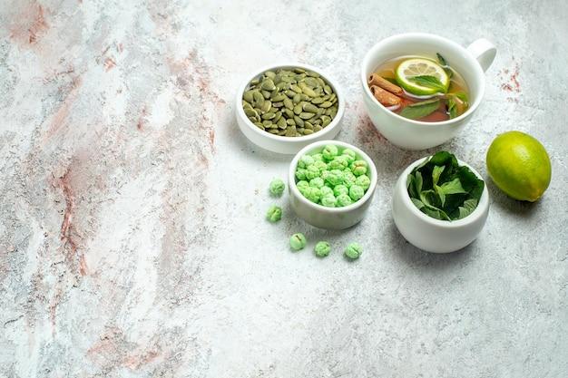 Xícara de chá com doces em um espaço em branco de vista frontal