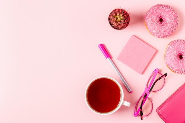 Xícara de chá com donuts em um fundo rosa pastel