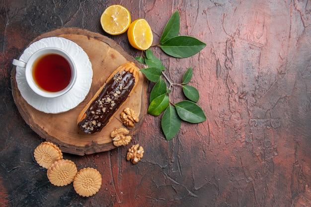 Xícara de chá com éclair e biscoitos em um bolo doce de biscoito de mesa escura com vista de cima