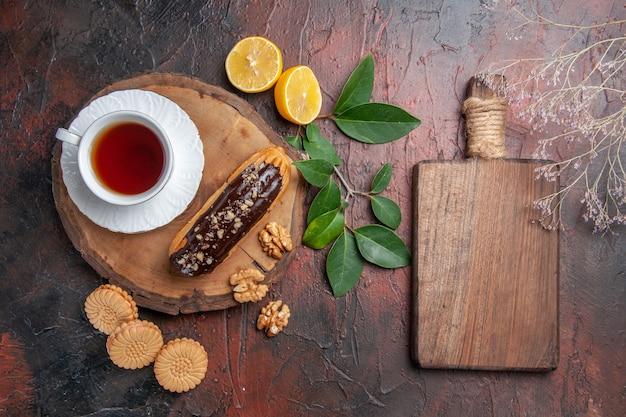 Xícara de chá com éclair e biscoitos na mesa escura de bolo de biscoito doce com vista de cima