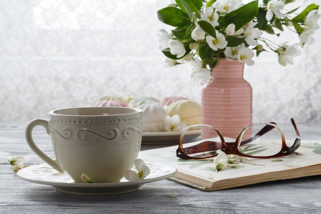 Xícara de chá com flor de cerejeira primavera e livro velho em uma parede de madeira