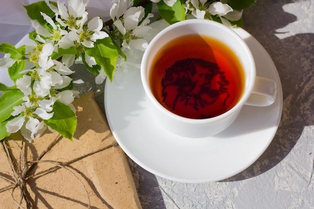Xícara de chá com flor de primavera fresca. café da manhã ao ar livre em dia de sol. bonita caixa de presente embrulhada em papel artesanal marrom simples e decorada com juta. conceito de preparação para as férias