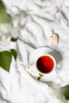 Xícara de chá com flores com biscoitos de coração em uma manta branca