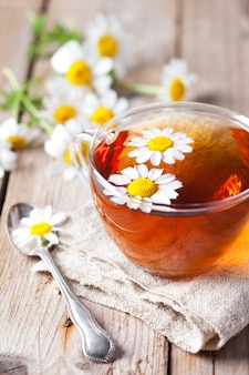 Xícara de chá com flores de camomila