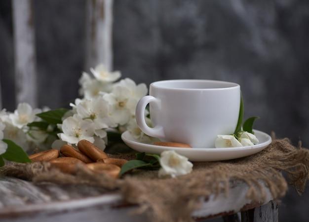 Xícara de chá com flores de jasmim em uma cadeira vintage