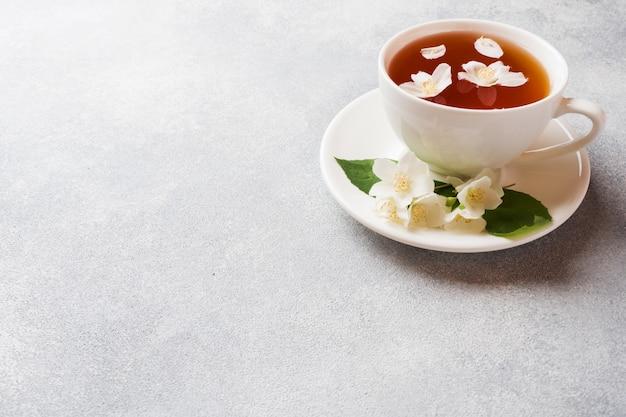 Xícara de chá com flores de jasmim em uma mesa cinza
