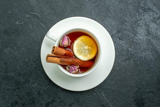 Xícara de chá com flores e chá na superfície escura de chá com frutas cítricas