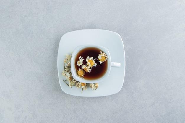 Xícara de chá com flores secas de camomila.