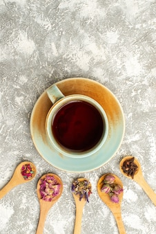 Xícara de chá com flores secas na superfície branca chá com sabor de flor