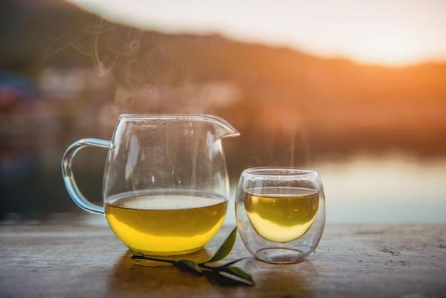 Xícara de chá com folhas de chá verde na mesa de madeira.
