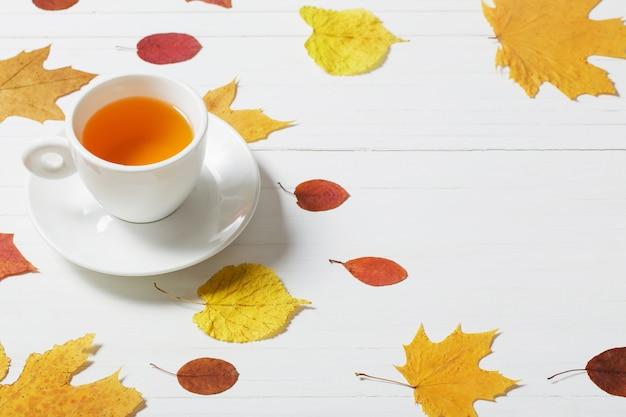 Xícara de chá com folhas de outono na parede de madeira