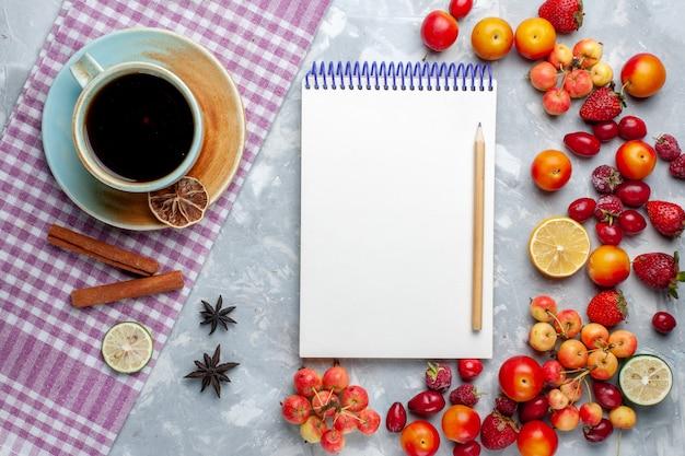 Xícara de chá com frutas, canela e bloco de notas na mesa de luz com frutas, frutas e frutas vitamina fresca
