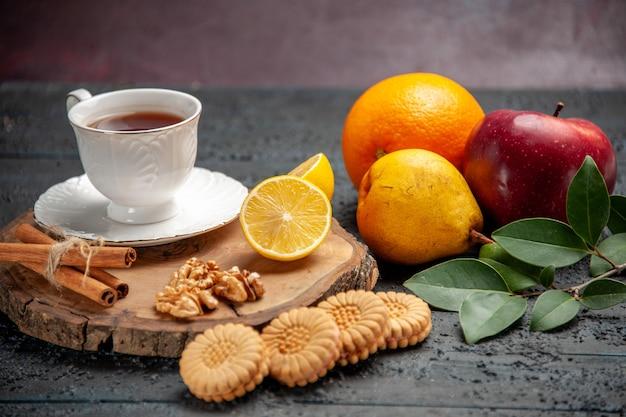 Xícara de chá com frutas e biscoitos na mesa escura de frente