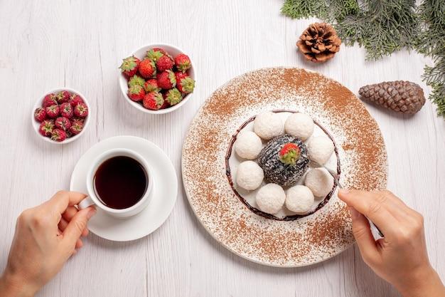Xícara de chá com frutas e doces de coco na mesa branca com bolo de bolacha de frutas e chá de frutas