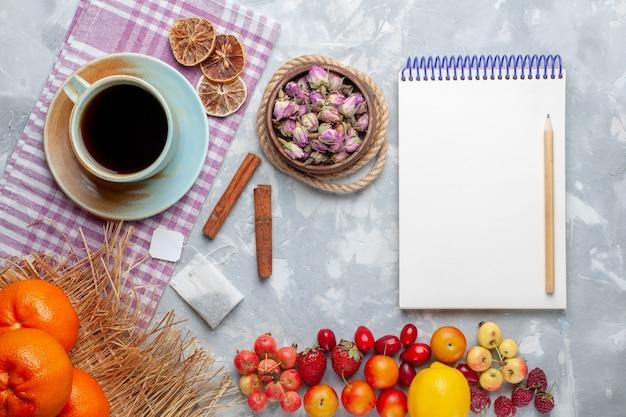 Xícara de chá com frutas na mesa branca com vista de cima