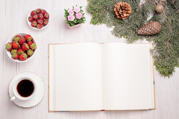 Xícara de chá com frutas na mesa branca, vista superior, chá, baga, bolo