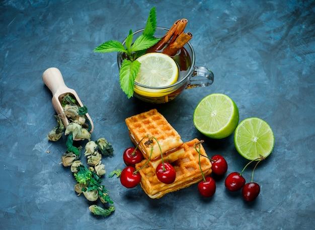 Xícara de chá com hortelã, canela, ervas secas, cereja, limão na superfície azul suja, plana leigos.